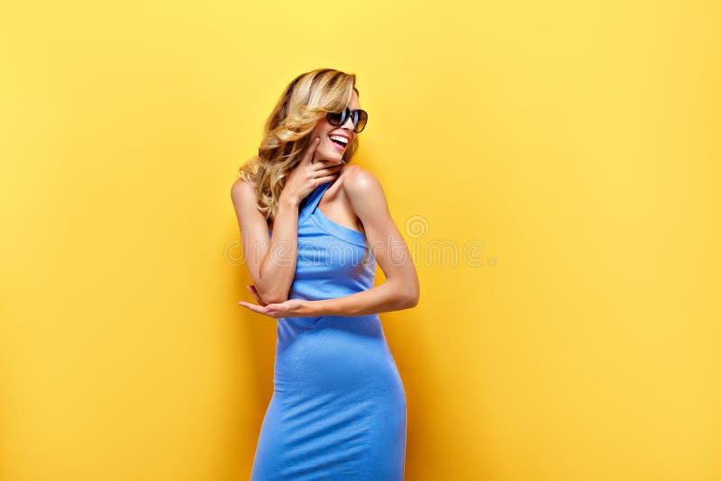 Den lyckliga blonda kvinnan i blått klär på gul bakgrund arkivfoto