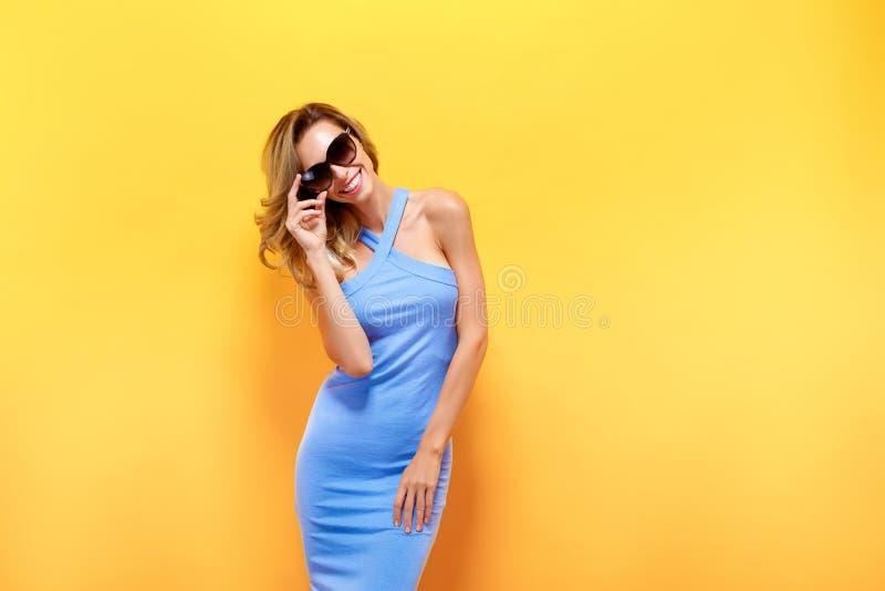 Den lyckliga blonda kvinnan i blått klär på gul bakgrund royaltyfri foto