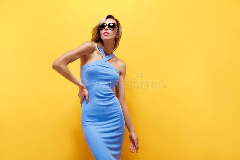 Den lyckliga blonda kvinnan i blått klär på gul bakgrund royaltyfri fotografi