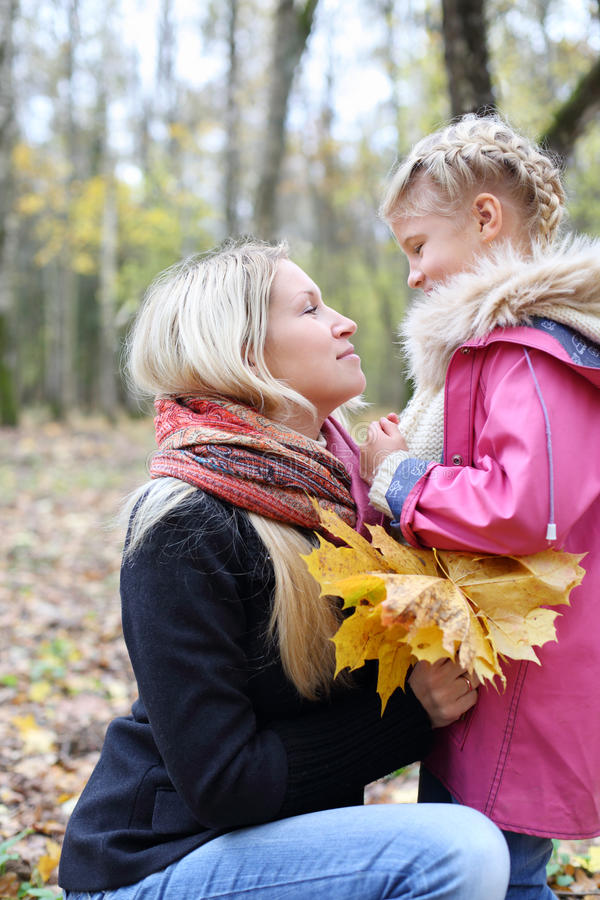 Den lyckliga blonda modern med lönnbroschyrer ser dottern royaltyfri bild