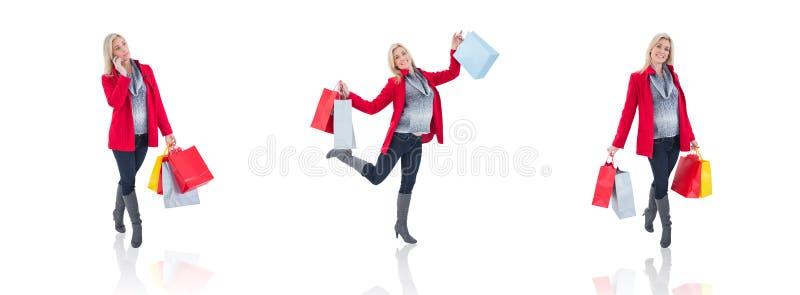 Den lyckliga blondinen i vinter beklär hållande shoppingpåsar royaltyfri foto