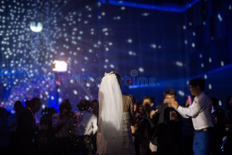Den lyckliga bruddansen på brölloppartiet med gäster och färg ledde att tända royaltyfri foto