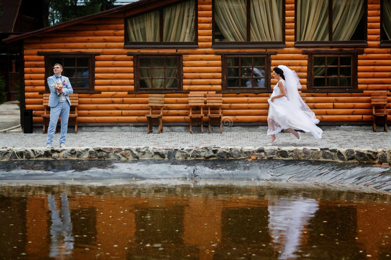 Den lyckliga bruden kör till en brudgum längs lite sjön royaltyfri bild