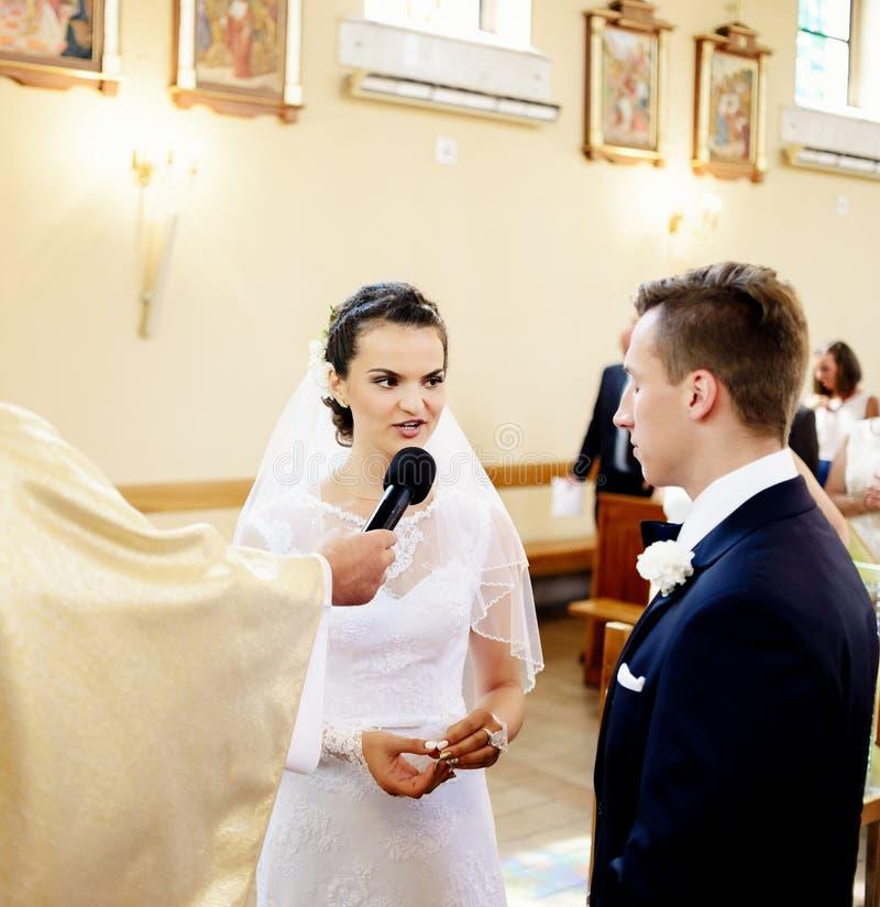 Den lyckliga bruden lovar för att älska den framtida maken i kyrkan arkivfoton