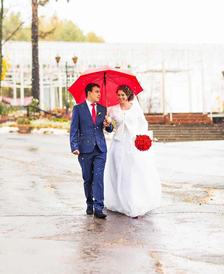 Den lyckliga bruden och brudgummen på bröllop går med det röda paraplyet Höststilbegrepp royaltyfri foto