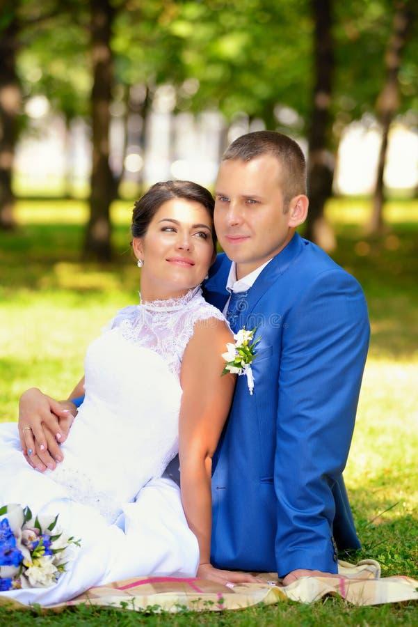 Den lyckliga bruden och brudgummen på deras bröllop sitter på gräset parkerar in arkivbild