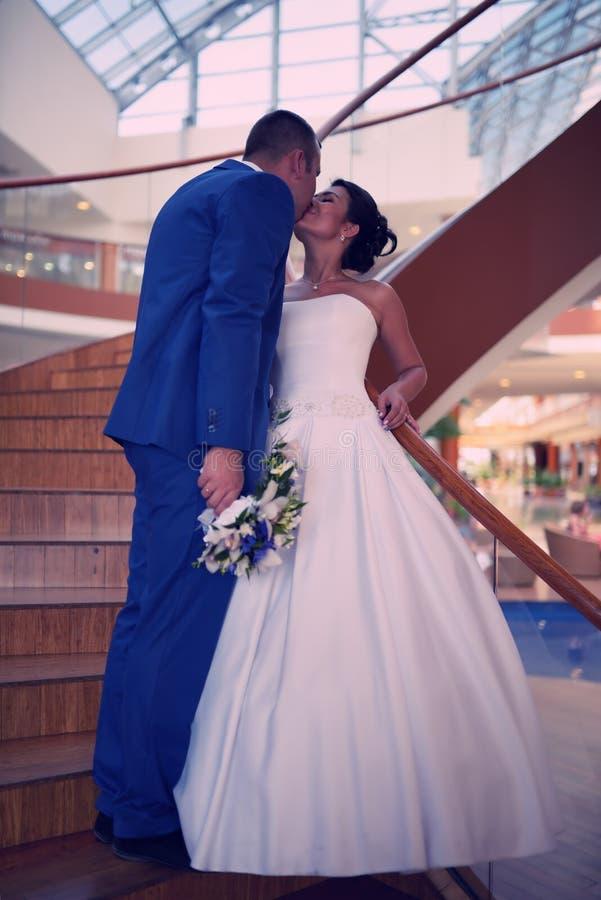 Den lyckliga bruden och brudgummen på deras bröllop står på en trästege arkivfoto