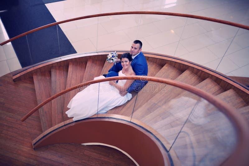 Den lyckliga bruden och brudgummen på deras bröllop står på en trästege fotografering för bildbyråer