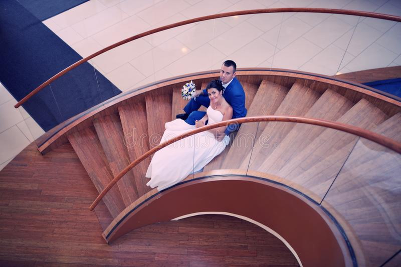 Den lyckliga bruden och brudgummen på deras bröllop står på en trästege royaltyfri foto