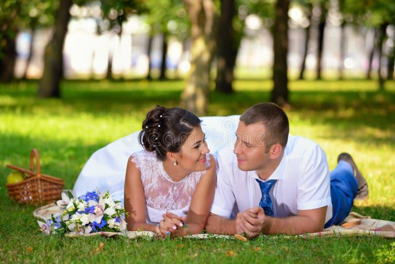 Den lyckliga bruden och brudgummen på deras brölloplögner på gräset parkerar in royaltyfria foton