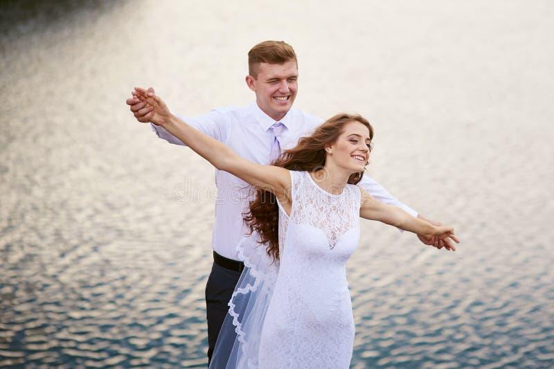 Den lyckliga bruden och brudgummen på ett bröllop går nära sjöomfamningen arkivbilder
