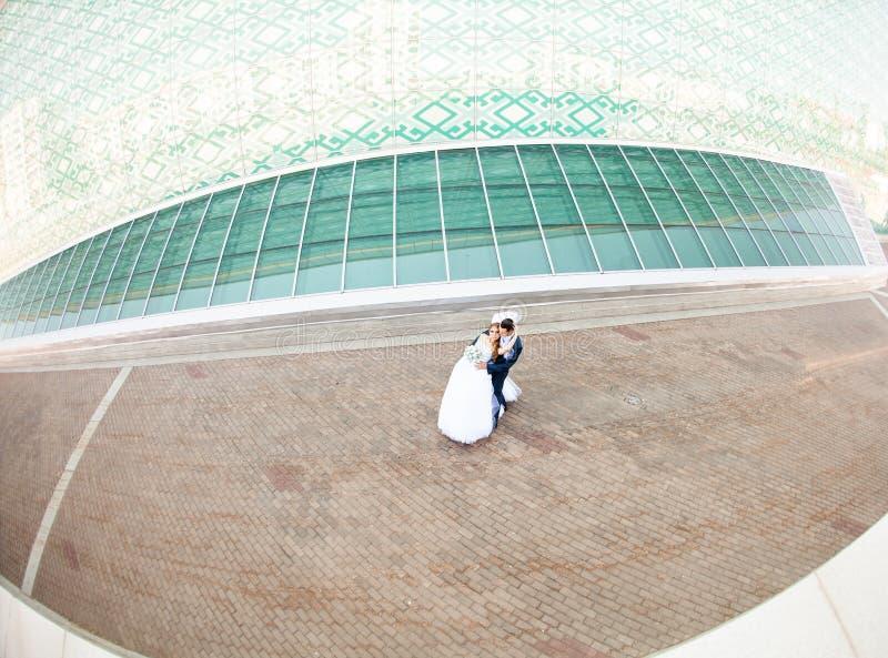 Den lyckliga bruden och den eleganta brudgummen i blått passar med royaltyfri bild