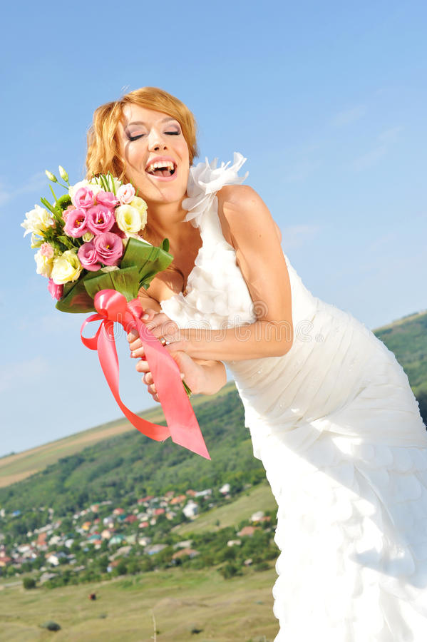 Den lyckliga bruden poserar med buketten royaltyfri bild