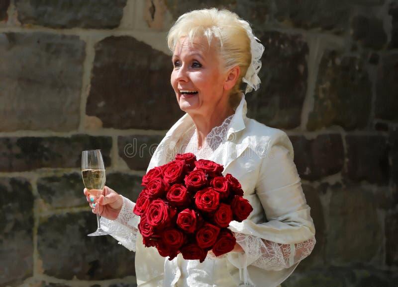 Den lyckliga bruden välkomnar hennes bröllopgäster efter bröllopceremonin framme av den gamla slotten till bröllopberömmen royaltyfri fotografi