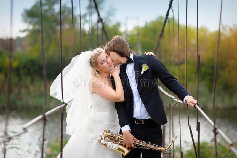Den lyckliga brudgummen kysser bruden på bron i deras bröllopdag arkivbild