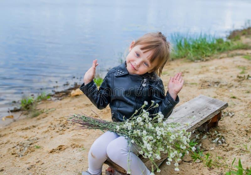 Den lyckliga caucasian flickan i vildblommor för omslagshåll a bredvid en sjö i parkerar fotografering för bildbyråer