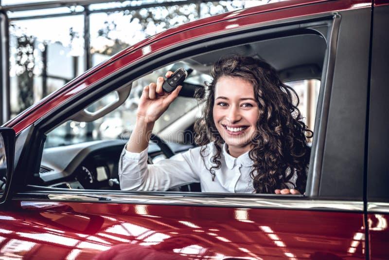 Den lyckliga chauffören för den unga kvinnan som rymmer automatiskn, stämmer i hennes nya moderna lyxiga bil arkivfoton
