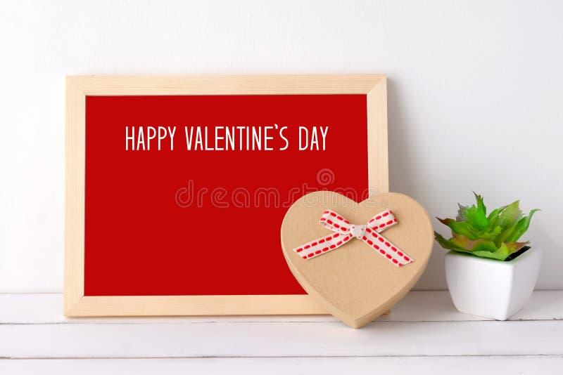 Den lyckliga dagen för valentin` s på det wood brädet och hjärta formar på gåvaasken royaltyfri bild