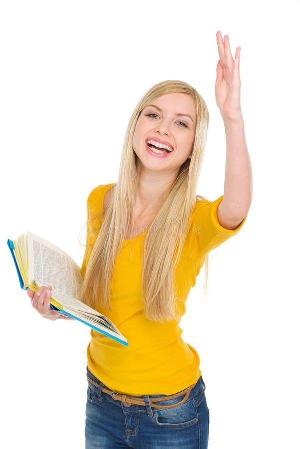 Den lyckliga deltagareflickan med bokar resning räcker till svaret royaltyfria bilder