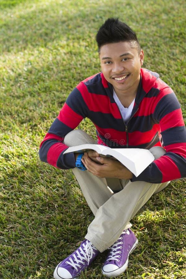 Den lyckliga deltagaren med bokar på lawn royaltyfri bild