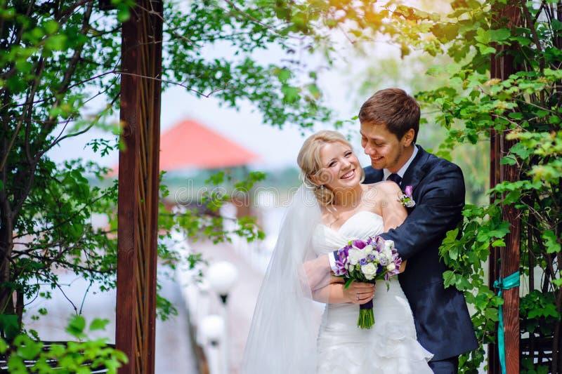Den lyckliga den bröllopparbruden och brudgummen parkerar in royaltyfri bild