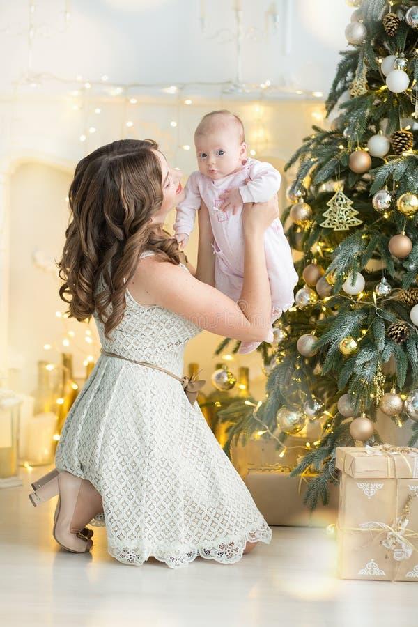 Den lyckliga det familjmodern och barnet behandla som ett barn pojken på julmorgon på trädet med gåvor, hem- garnering, inre hus royaltyfri fotografi