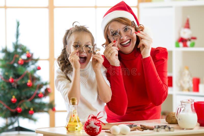 Den lyckliga det familjmodern och barnet har en gyckel som förbereder degen Kvinnan och dottern bakar julkakor i festival arkivbilder