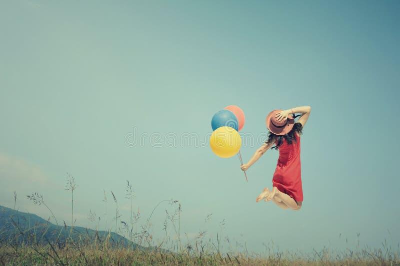 Den lyckliga det kvinnabanhoppningen och innehavet sväller med utomhus- blå himmel Inte gör de ser smaskiga fotografering för bildbyråer