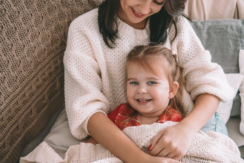 Den lyckliga dottern och en moder som skrattar på sängen arkivfoto