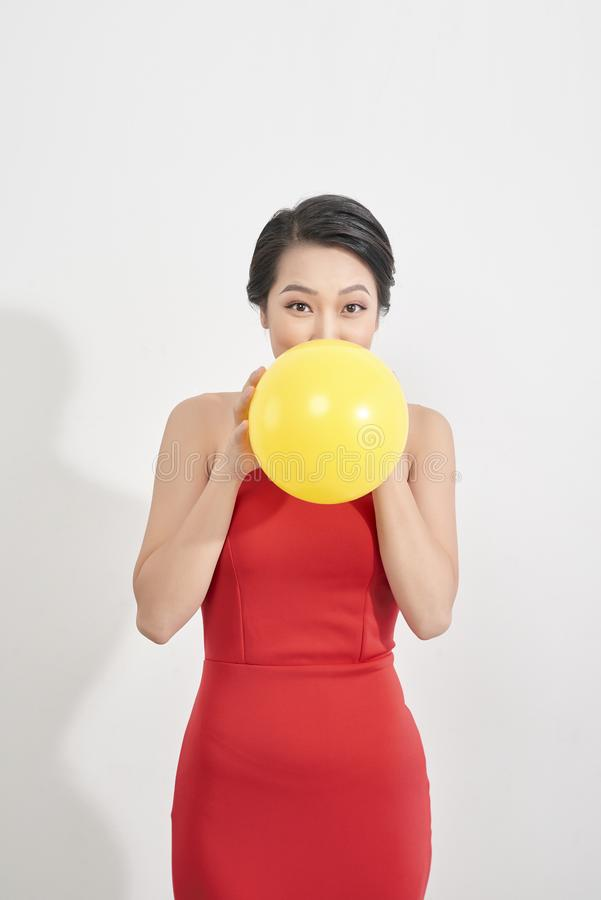 Den lyckliga emotionella unga asiatiska kvinnan i rött blåser en gul ballong i studio Stående av den härliga vietnamesiska flicka arkivfoton