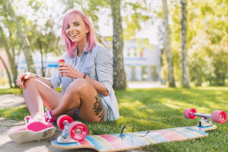 Den lyckliga europeiska härliga le kvinnan med att blåsa rosa hår med glass i handen som in sitter, parkerar på grönt gräs royaltyfria bilder