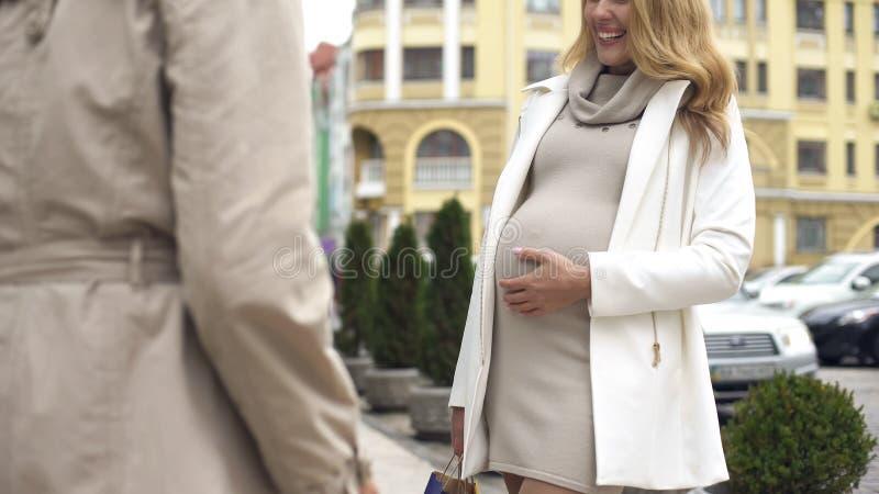 Den lyckliga förväntande modern som slår magen som talar till vänstadsgatan, råder arkivfoto