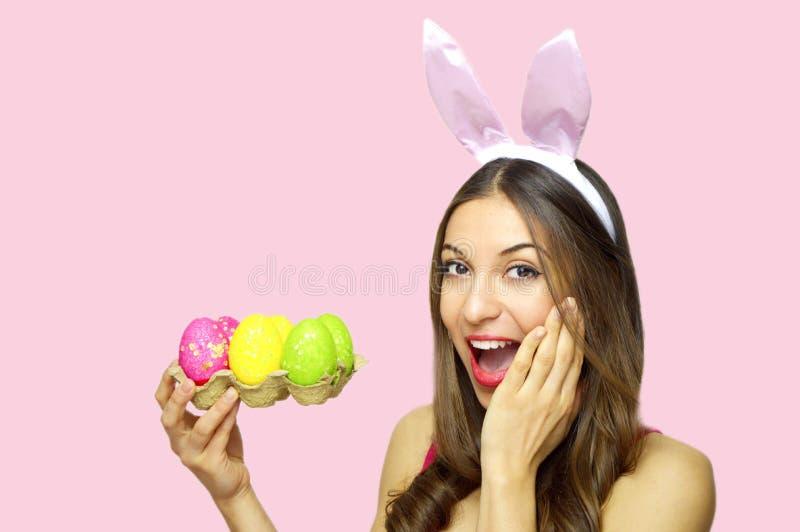 Den lyckliga förvånade kvinnan med kaninen gå i ax innehavägglådan av färgrika påskägg som ser kameran över rosa bakgrund Kopieri arkivfoto