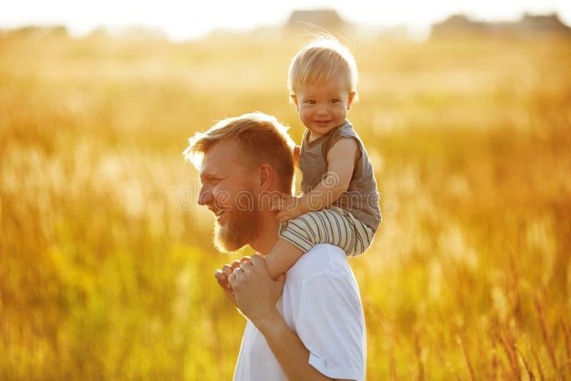 Den lyckliga fadern bär hans son arkivfoton