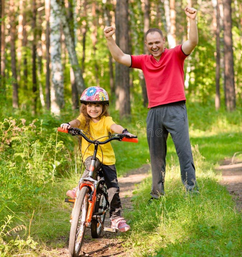Den lyckliga fadern jublar att hennes lärda dotter för att rida en cykel royaltyfri foto