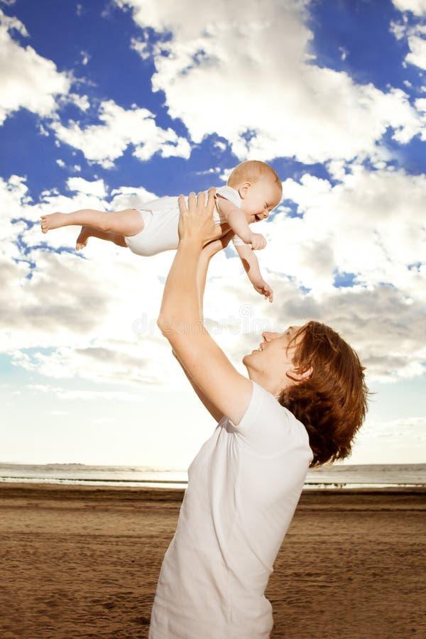 Den lyckliga fadern kastar behandla som ett barn upp pojken mot blå himmel royaltyfri foto