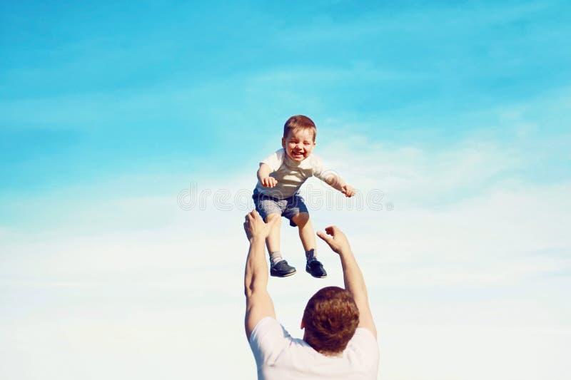 Den lyckliga fadern kastar sonbarnet in i luften, arkivfoto