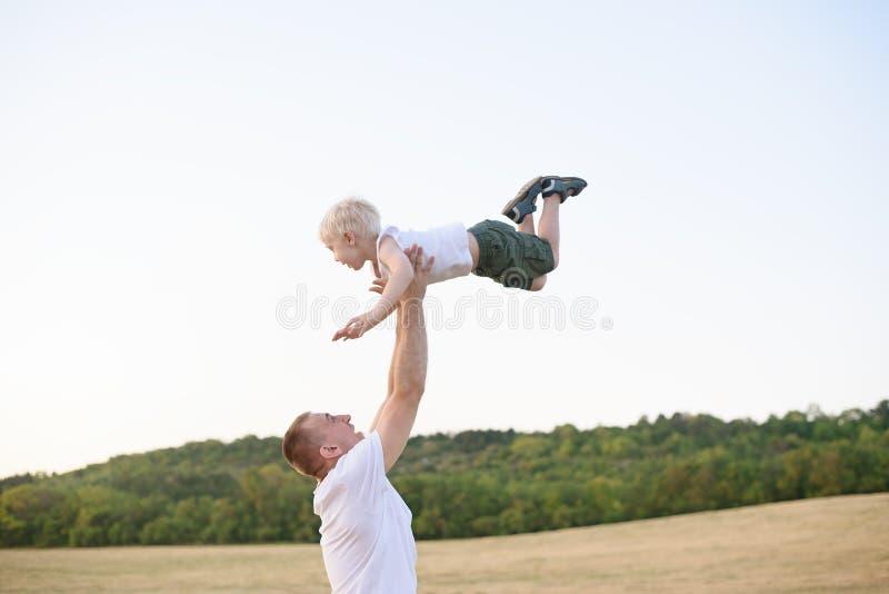 Den lyckliga fadern kastar upp lite den blonda pojken p arkivbild