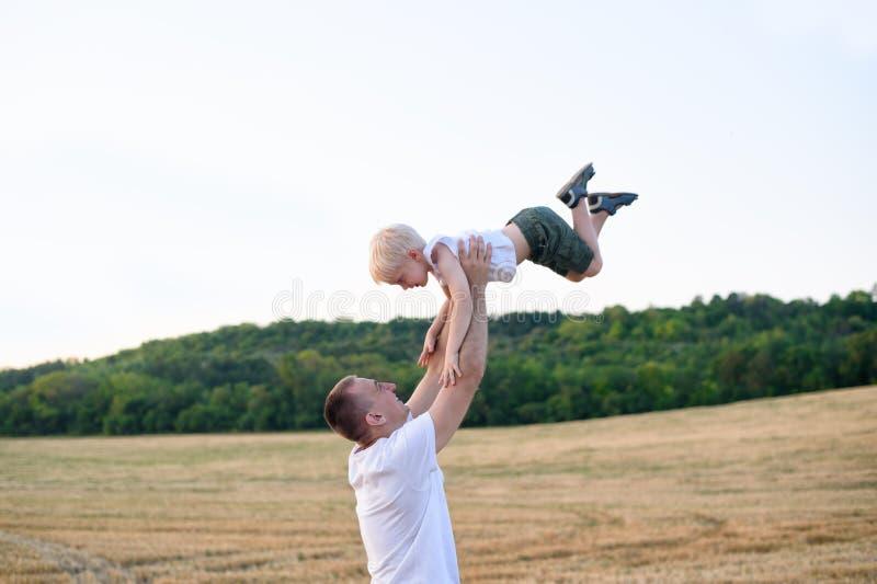 Den lyckliga fadern kastar upp lite den blonda pojken p? ett mejat vetef?lt skjuten solnedg?ngtid f?r exponering long arkivbild