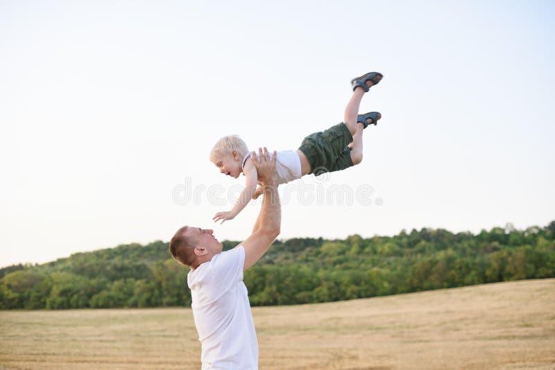 Den lyckliga fadern kastar upp lite den blonda pojken p? ett mejat vetef?lt skjuten solnedg?ngtid f?r exponering long royaltyfri fotografi