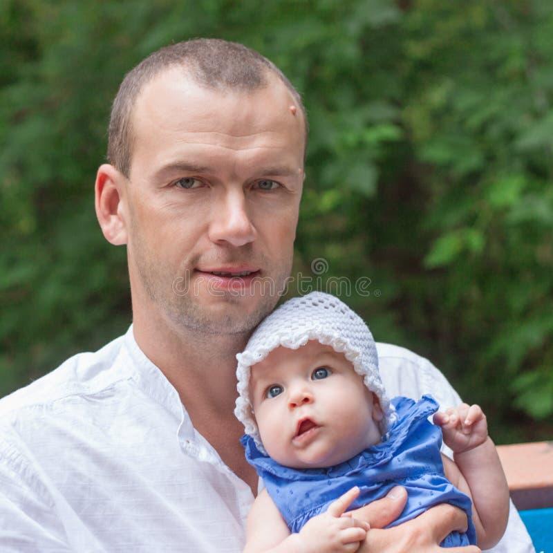 Den lyckliga fadern kramar försiktigt den lilla dottern arkivbilder