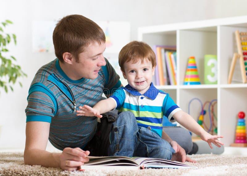 Den lyckliga fadern läste en bok till barnet arkivfoto