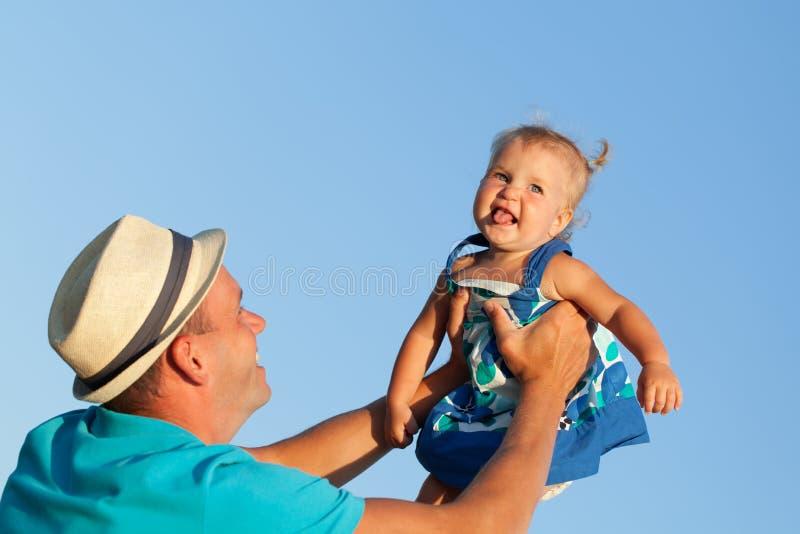 Den lyckliga fadern lyfter höjdpunkt hennes lilla nätta flicka på bakgrund för blå himmel royaltyfri foto