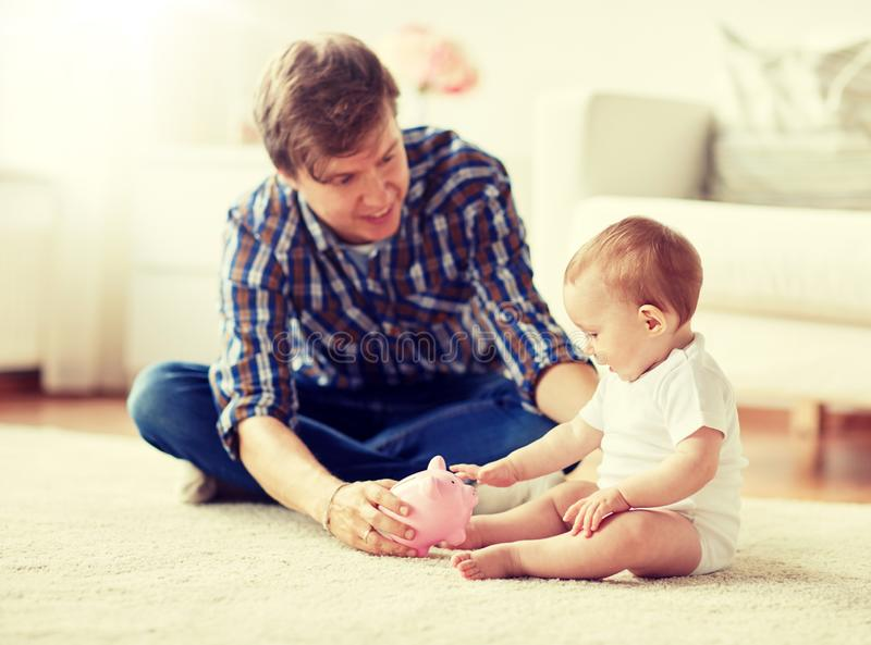Den lyckliga fadern med behandla som ett barn och spargrisen hemma royaltyfri bild