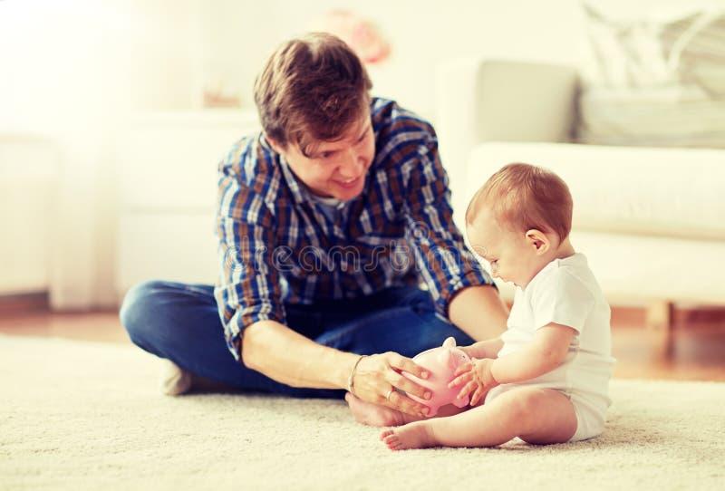 Den lyckliga fadern med behandla som ett barn och spargrisen hemma royaltyfri fotografi