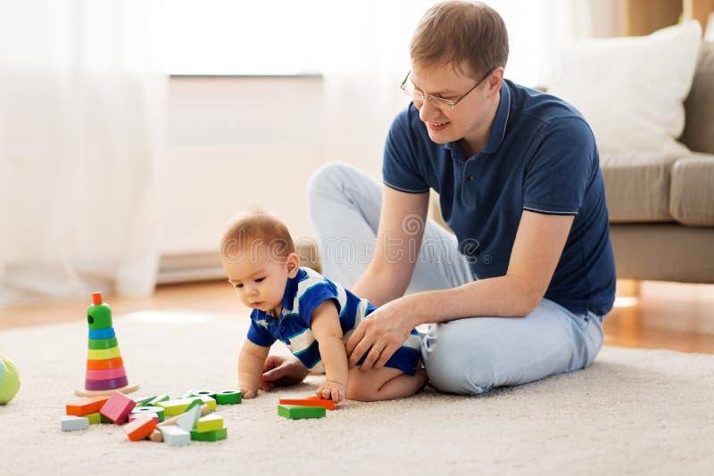 Den lyckliga fadern med behandla som ett barn sonen som hemma spelar leksaker royaltyfri bild