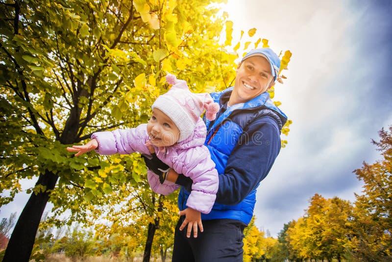 Den lyckliga fadern med ett litet barn i hösten parkerar arkivfoton