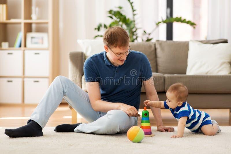 Den lyckliga fadern med litet behandla som ett barn sonen som hemma spelar royaltyfria foton