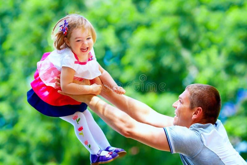 Den lyckliga fadern och behandla som ett barn flickan som har gyckel parkerar in arkivbilder