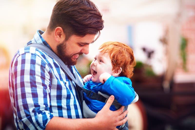 Den lyckliga fadern och behandla som ett barn sonen i remryggsäcken som har en gå i staden royaltyfri fotografi